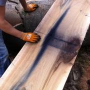 gesägte Holzscheibe mit Granatenspuren aus dem letzten Weltkrieg.